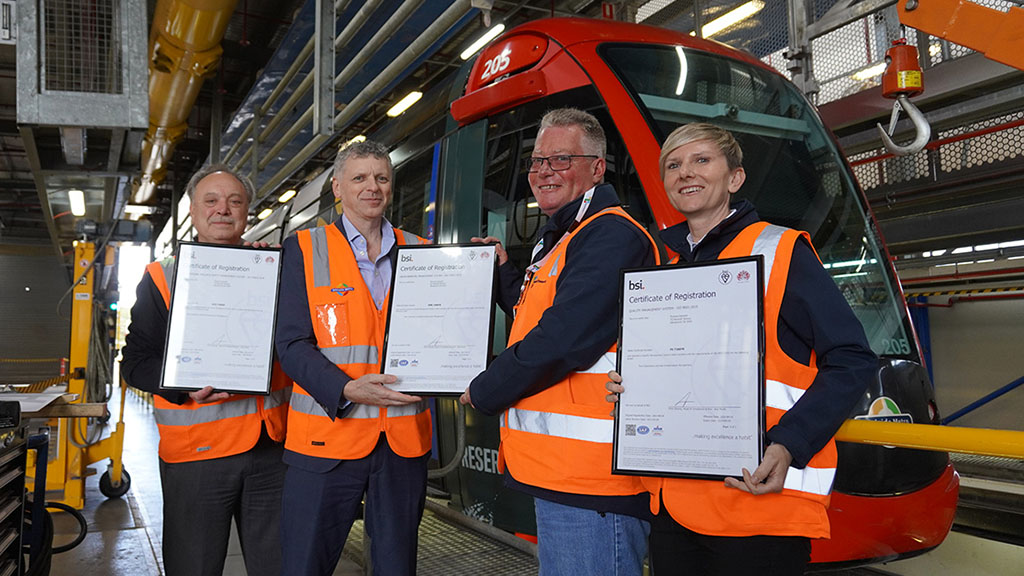 Four people holding certificates in front of a tram