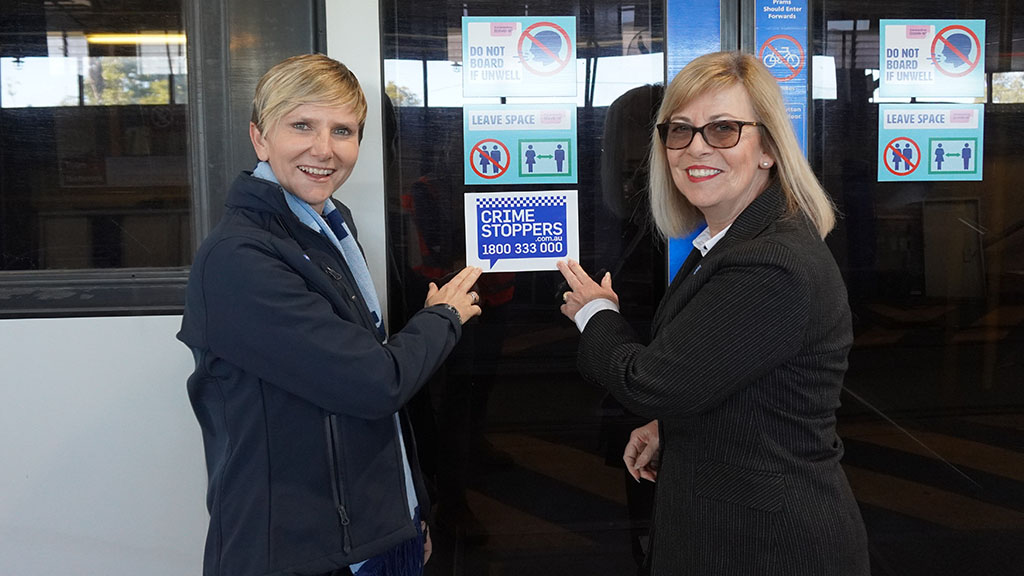 Two people pointing to a CrimeStoppers badge on a tram door