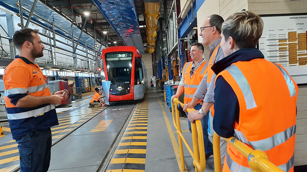 The Minister being shown the tram maintenance barn as a tram is undergoing a vinyl wrap in the background.