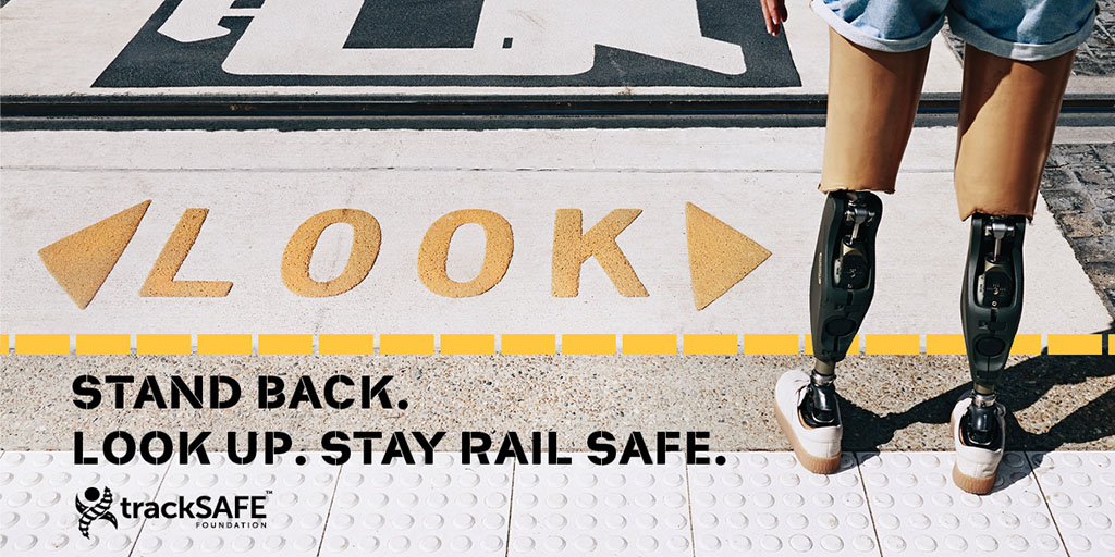 Person with 2 prosthetic legs standing on a platform behind the yellow line. Text reads: Stand back. Look up. Stay rail safe.
