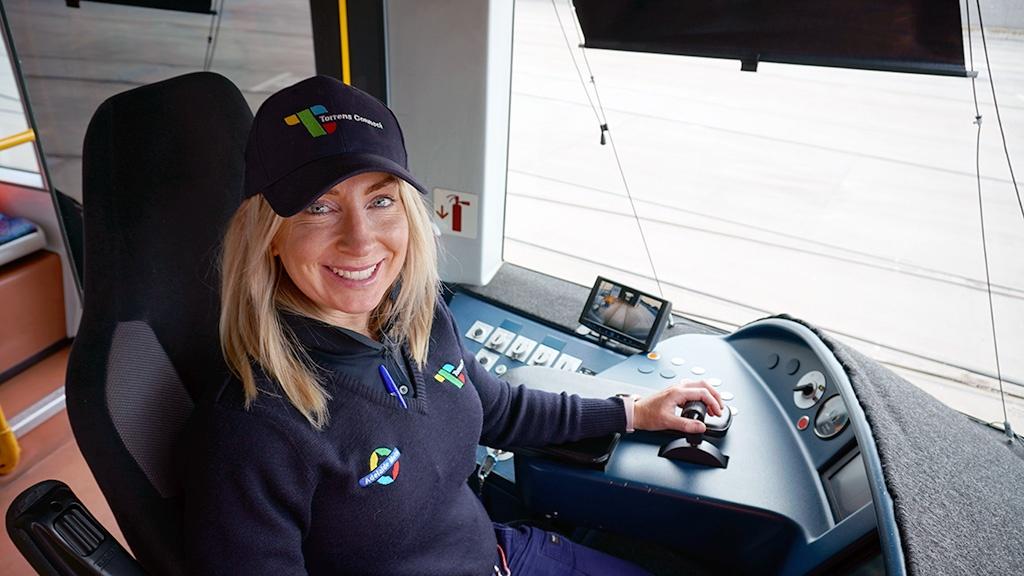 A female tram operator seated in the tram driver's cab