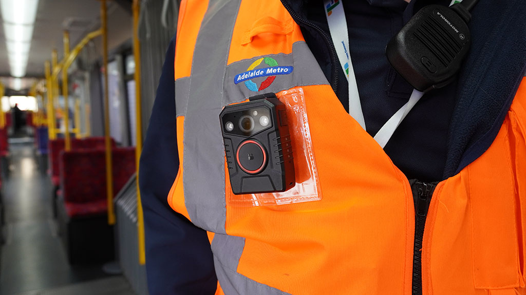 Close up of a body-worn camera attached to a hi-vis vest worn by a Customer Service Officer on board a tram
