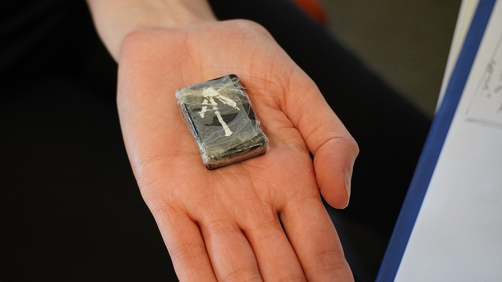A small data logger held in the palm of a hand