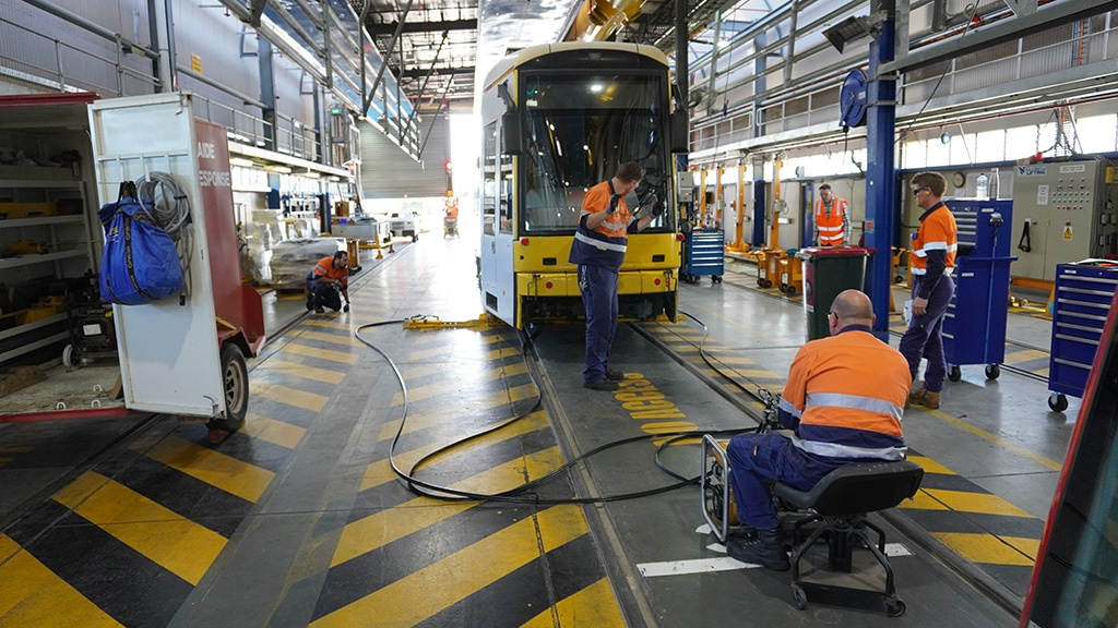 Maintenance Team jacking up a Flexity tram in the barn