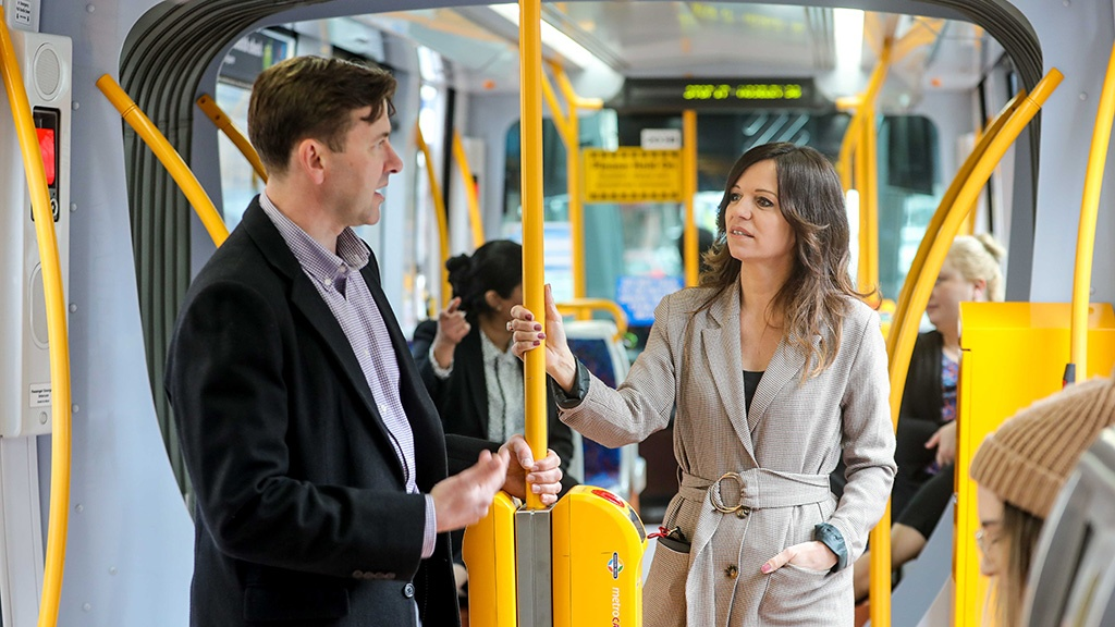 A male and female customer travelling in a tram, standing up and holding on to the yellow pole.