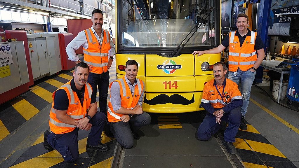 Torrens Connect employees with a tram, all sporting mos.