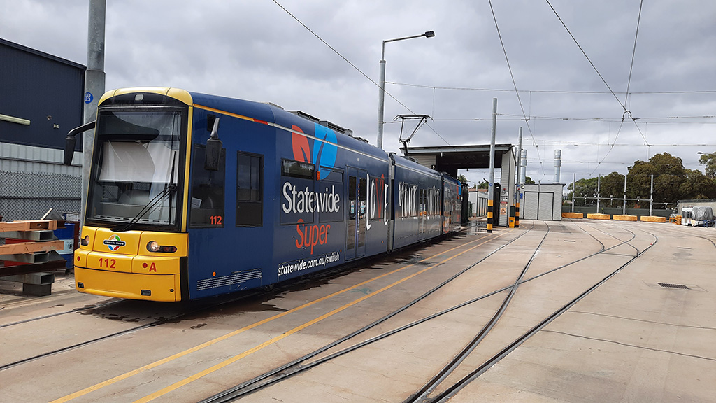 A tram stopped in front of the tram wash bay